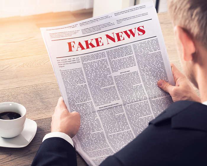 """Persona leyendo """"fake news"""" en un periódico"""