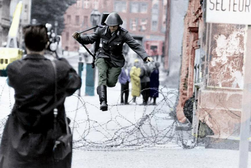 Conrad Schumann fue el primer soldado desertor de la República Democrática de Alemania, cruzando el 15 agosto de 1961 por una sección incompleta del muro a la República Federal de Alemania. El momento fue inmortalizado gracias a Peter Leibing. Todos los derechos a quien haya coloreado la fotografía.